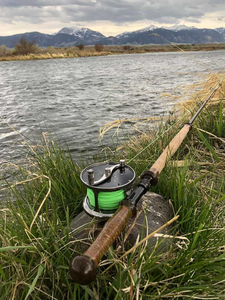 meiser rod and reel leaning on ground in front of river